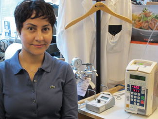 Sharareh Taghipour stands next to a medical infusion pump. She and a colleague developed a model to determine the optimal inspection interval for such pumps and other devices.