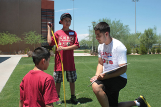 Sergio Ortiz, a University of Arizona engineering student, discusses the correct technique for measuring your strike zone with two students.