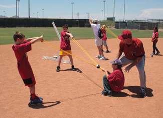 Coach Sean Payton of the Arizona Diamondbacks makes suggestions on the optimal angle of trajectory that will maximize travel distance for a baseball while three students use a water balloon launcher to test the hypothesis. The optimal trajectory to hit a home run is 35 degrees.