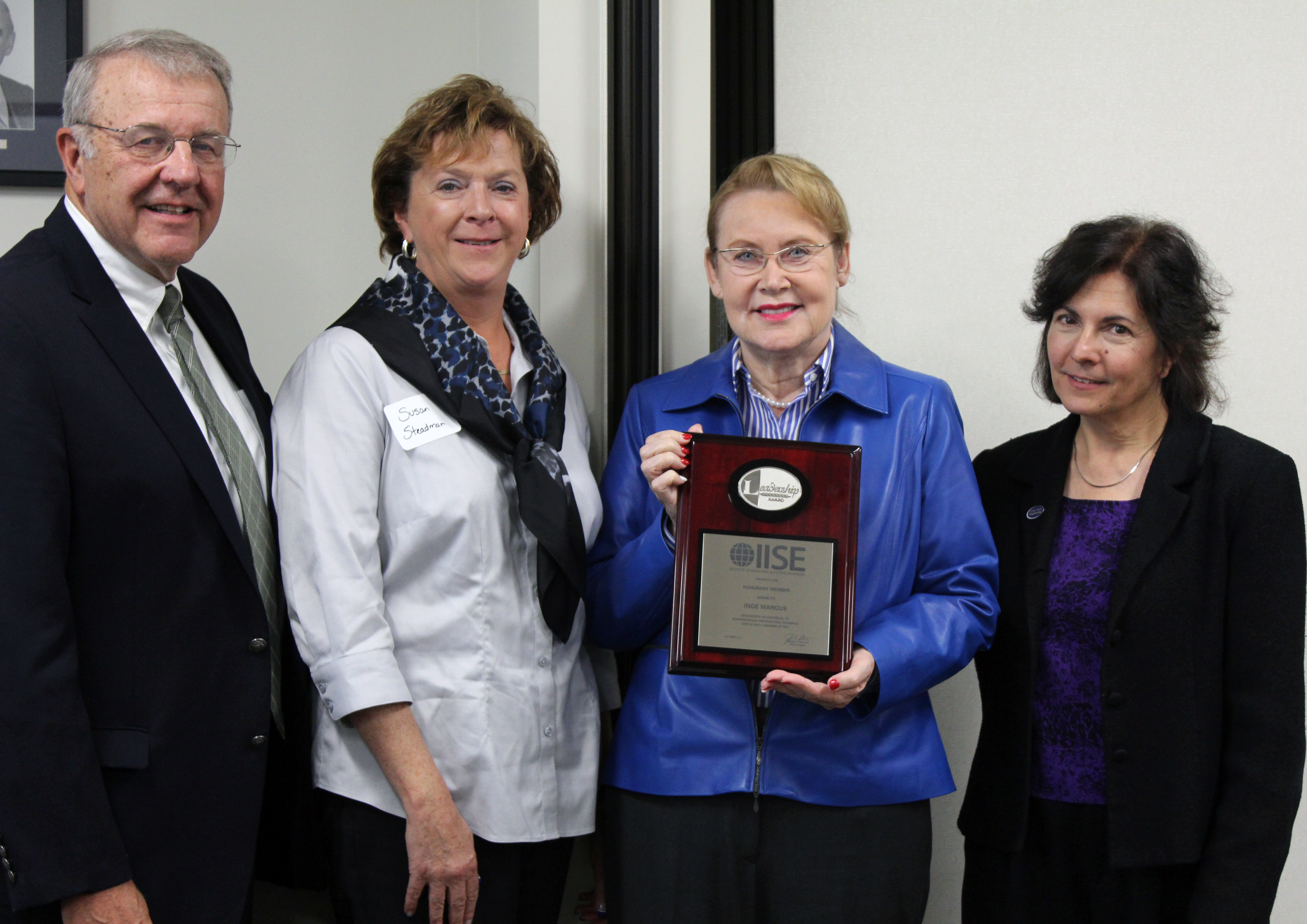"Inge Marcus (pictured holding plaque) was presented with an honorary membership to the Institute of Industrial and Systems Engineers (IISE) at an Oct. 20, 2017, ceremony at The Pennsylvania State University campus in celebration of the life and contributions of Marcus and her late husband Harold ""Hal"" Marcus. Former IISE Presidents Alan Soyster (left), a former head of the Harold & Inge Marcus Department of Industrial & Manufacturing Engineering (IME), and Susan Steadman, also an IME alumna, along with Peter and Angela Dal Pezzo Department Head Janis Terpenny (right), presented Marcus with the plaque on behalf of IISE. (Pam Wertz/Penn State)"